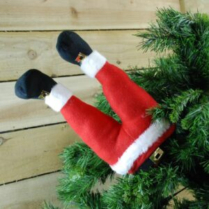 red santa legs coming out of the christmas tree